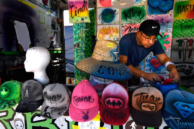 Marvin Ramirez pulls out an order for a custom design Wednesday in his First Class Airbrush booth at the West Texas Fair & Rodeo.