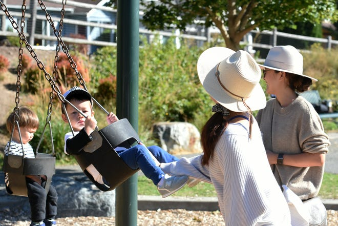 Motome Devery, left, plays with her son, 2, at the swings at Kiwanis Park in Bremerton on Thursday. The Bremerton Kiwanis Club has announced it will donate money to the city for accessibility improvements at the park