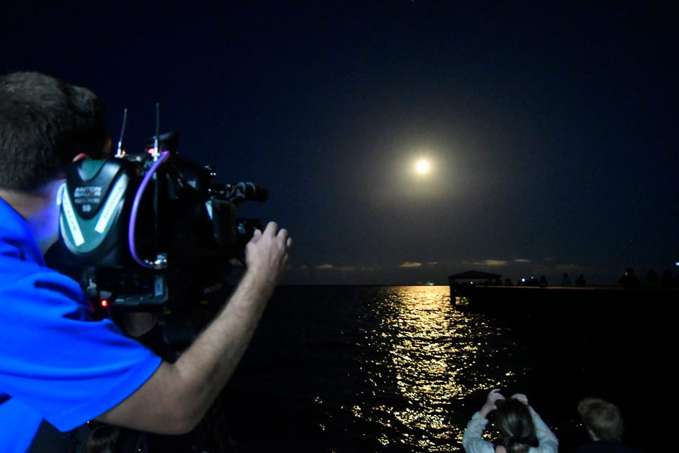 A man captures the launch of SpaceX's Falcon 9 rocket.