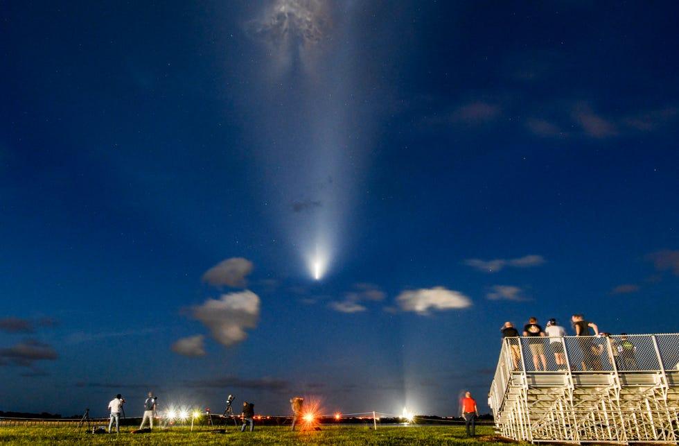 Spectators watch as the Falcon 9 rocket starts its journey into orbit.