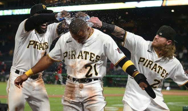 Sep 15, 2021; Pittsburgh, Pennsylvania, USA;  Pittsburgh Pirates outfielders Anthony Alford (left) and Ben Gamel (right) pour water on pinch hitter Wilmer Difo (front) after Difo scored the game winning run to defeat the Cincinnati Red at PNC Park. The Pirates won 5-4. Mandatory Credit: Charles LeClaire-USA TODAY Sports
