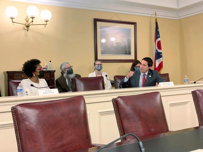 Ohio Elections Chief Frank LaRose, right, talks about his desire for a new, 10-year map of the state's legislative districts at a meeting of the Ohio Redistricting Commission on Tuesday, Aug. 31, 2021 in Columbus, Ohio, as fellow commission member Rep. Emilia Sykes of Akron, the top House Democrat, listens to his statement. LaRose, a Republican, this week launched a new effort to purge inactive voters from state rolls. (AP Photo/Andrew Welsh-Huggins)
