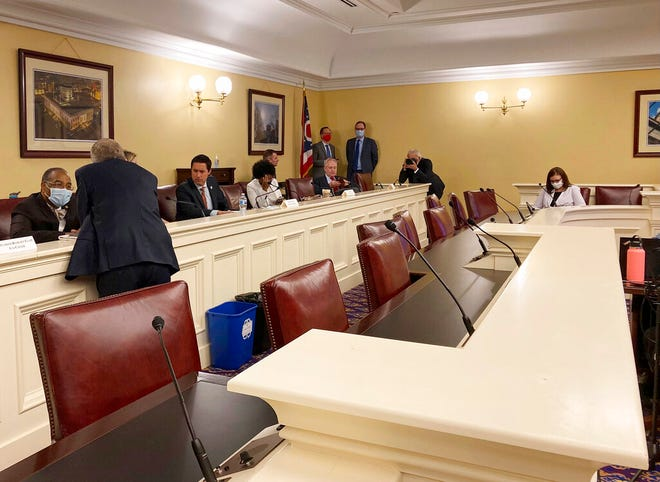 Republican Ohio Gov. Mike DeWine, foreground, speaks to state Sen. Vernon Sykes, seated, the co-chair of the Ohio Redistricting Commission, as other members of the panel prepared for a meeting on Wednesday, Sept. 15, 2021, at the Ohio Statehouse in Columbus, Ohio. (AP Photo/Julie Carr Smyth)