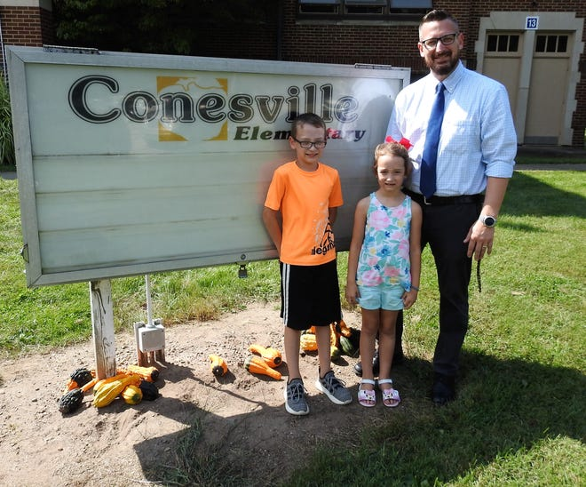 Jarred Renner with his children Caden and Kensington at Conesville Elementary, where he serves as principal. He hopes to be a leadership role model for them as his father and principals were for him. Renner recently won the Younger Leader of the Year Award from the Coshocton County Chamber of Commerce.