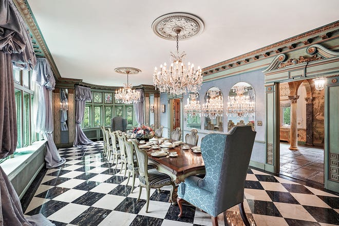The lavish dining room has blue velvet walls, a marble floor and heavy carved woodwork. It's glazed with blue, green and gold leaf. Two crystal chandeliers and five crystal sconces bounce light off its surfaces.