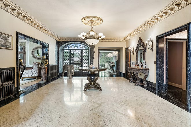 The grand foyer has deep carved molding and a floor of white-with-black marble. An elephant keeps guard inside the door, which is filigreed wrought iron.