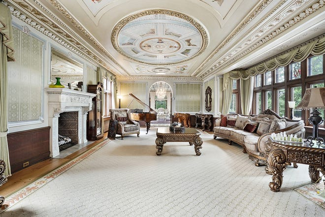 Almost 3 feet of crown molding frame the living room's barrel-shaped ceiling. It is embellished with carved plaster designs, painted angels and gold leaf.