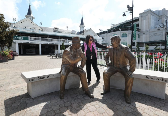Churchill Downs box office sales employee Teresa Peals touches the statue of John Asher after the statues of Asher and Col. Matt Winn, left, were unveiled Thursday in the paddock area at the track in Louisville, Ky. on Sep. 16, 2021.  Peals says that she would say hello to Asher on occasion.
