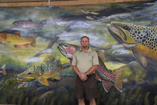 Jon Casey, project leader for the Norfork National Fish Hatchery, stands in front of Duane Hada's trout mural. The Norfork hatchery raises roughly 1.2 million trout per year.