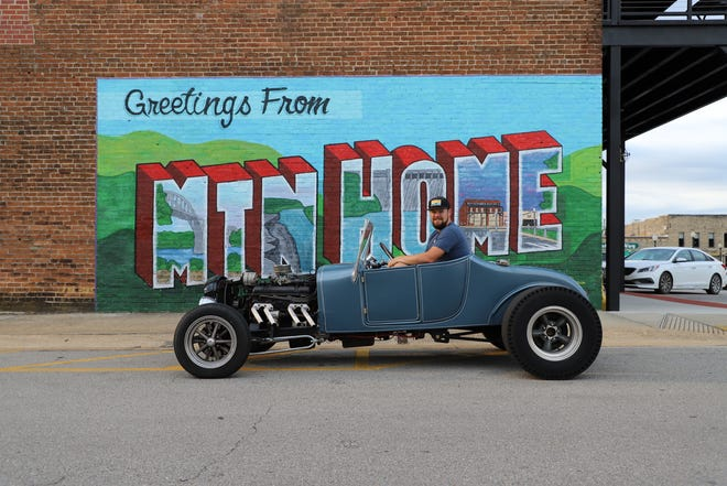 Corey McMahon poses for a photo in his Ford Model T outside of Rapp's Barren Brewery's new mural.