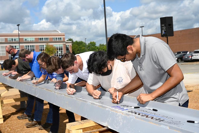 MTSU students sign the ceremonial final beam to be placed at the top of the School of Concrete and Construction Management building Tuesday, Sept. 14, in the Bragg Parking lot adjacent to the construction site. The 54,000-square-foot building is expected to be completed in 15 months, in time for Fall 2022 classes. The facility features classrooms, faculty and staff offices and laboratory space for Concrete Industry Management and Construction Management, both of which provide interns and ready-to-work graduates awaiting potentially lucrative careers. (MTSU photo by J. Intintoli)