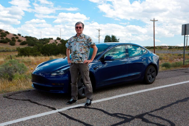 Howard Coe poses in front of his wife's Tesla sedan on Tuesday, Sept. 14, 2021, on a road near Nambé Pueblo outside of Santa Fe, N.M. Coe welcomed the opening of a new Tesla store and repair shop where he can pickup an SUV he's buying. Last year, he and his wife had to pick up her car in Denver, Colo., about five hours away, because of New Mexico laws that bar companies like Tesla from selling cars directly to customers.