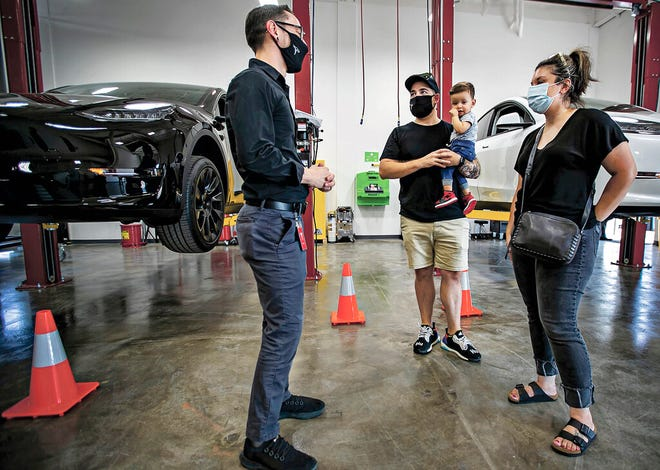 In this Sept. 9, 2021 photo, Tesla owners Joshua Vigil and Melanie Vigil, right, talk with Tesla service manager Brandon Arpin, left, during an event to celebrate a partnership between Tesla and the Nambé Pueblo after the electric car company repurposed a defunct casino into a sales, service and delivery center near Santa Fe, N.M. Tesla has opened a store on tribal land in New Mexico, sidestepping car dealership laws that prohibit car companies from selling directly to customers.