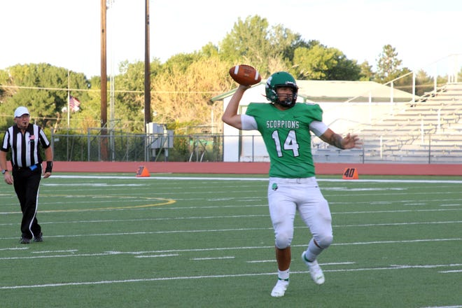 Farmington quarterback Brandon Furbee looks downfield before attempting a pass in the first quarter of the Scorpions 53-13 win over Belen, Friday, Aug. 27 at Hutchison Stadium