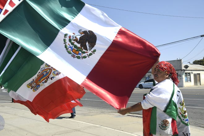 Agustin Marquez displays Mexican flags on sale for Mexican Independence Day.
