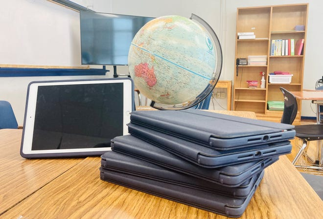 A stack of iPads purchased by San Angelo ISD are displayed on a desk.