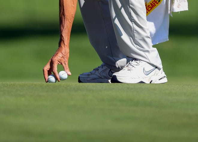 Bernhard Langer's caddy, Terry Holt, picks up Langer's golf balls during the pro-am competition at the Sanford International golf tournament on Thursday, September 16, 2021, at the Minnehaha Country Club in Sioux Falls.