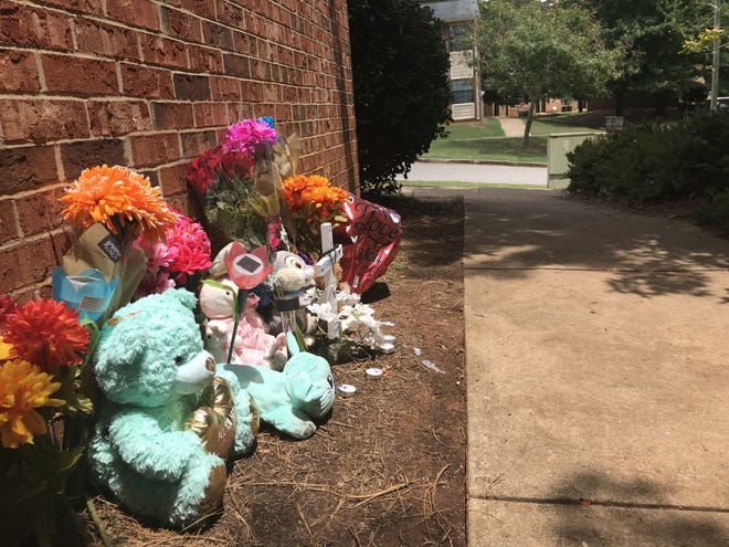 A memorial of flowers and stuffed animals was placed near where Auriel Callaway died in July 2019 at Clarke Garden Apartments.