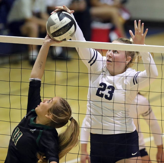 Archbishop Hoban's Megan Glinsky, right, pushes the ball over the next against STVM's Sophia Littler during the first set of the Knights' volleyball win over the Irish on Thursday night. [Jeff Lange/Beacon Journal]