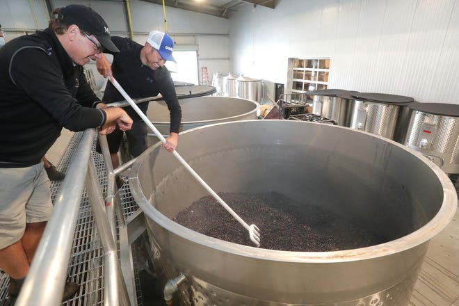 Michael Oravecz, left, and Mike Laszlo spread Grenache grapes into a stainless steel tank at Grand Cru Custom Crush on Sept. 1 in Windsor, California.