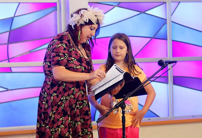 """Music coordinator Jessica Wagner helps Willow Jarrell find the right page to read during auditions for the Kroc Center's production of """"Frozen Jr."""" TOM E. PUSKAR/TIMES-GAZETTE.COM"""