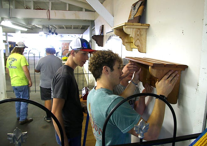 Mapleton High School students Jed Brannon, Andrew Sas and Seth Case hang a shelf as they set up the school's Industrial Tech display in the junior fair building on Friday, Sept. 17, 2021. TOM E. PUSKAR/TIMES-GAZETTE.COM