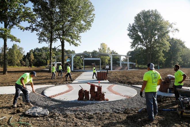 Members of the landscaping company Yard Solutions put the final touches on the new field Friday for Miracle League of New Albany. A grand opening for the event is scheduled for Oct. 2 and will feature at least two baseball games.