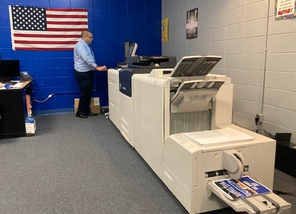 Buckeye Trail Business and Computer teacher Jerrod Norman works at the new Versant 280 Press by Xerox, part of the recent renovations in the lab. The print shop has opened new opportunities for students in the East Guernsey Local School District.
