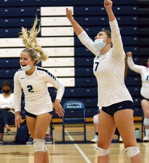 Petoskey players Jordyn Lake (2) and Jamie Sneddon (7) celebrate a point near the end of the second set of a three-set match win over Gaylord Thursday.