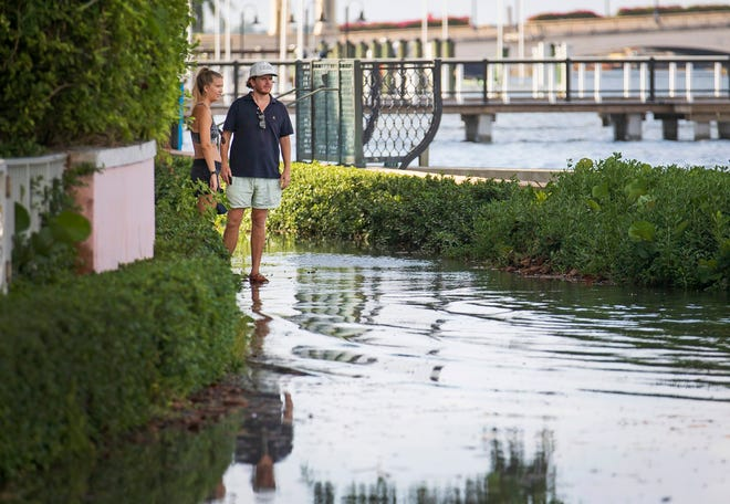 A couple looks at the flooded Lake Trail between Royal Palm Way and Royal Poinciana Way in Palm Beach on September 18, 2020 as the king tide season is underway.
