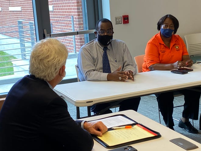 Virginia Attorney General Mark Herring, left, listens as Dr. George Lyons, center, pastor of Gillfield Baptist Church in Petersburg, speaks during a gun-violence roundtable at the Petersburg Public Library Friday, Sept. 17, 2021. Beside Lyons is Petersburg Sheriff Vanessa Crawford.