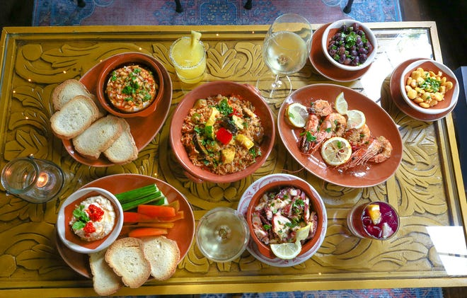 Tapas dishes at Aguardente include (clockwise from top right)  Marinated Olives, Lupini Beans,  Carabineros prawns,  chilled Marinated Octopus Salad, White Bean Dip, Queijo Fresco Portuguese dip and Vegetable Paella.  Drinks include the Hibisco-rita  and Foral Alvaninho wine.