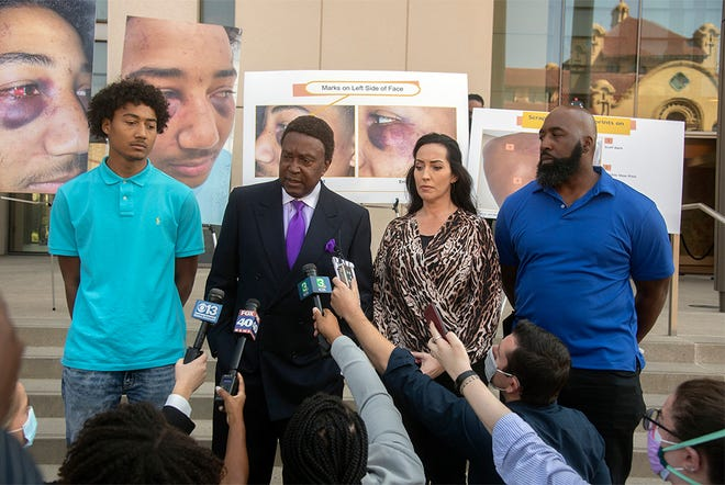 Civil rights attorney John Burris, second from left, stands with Devin Carter, left, and his parents Jessica Carter and George Carter on the steps of the San Joaquin County courthouse in downtown Stockton during a press conference announcing the indictment of 2 Stockton Police officers who are charged in the burial beating of Devin during a traffic Stockton in December of 2020.