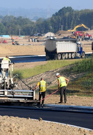 Workers apply fresh asphalt Friday morning to Sterilite Street SE toward its connection with Fohl Street SW in Navarre. The extension of Sterilite Street is to accommodate the construction of a new Tractor Supply warehouse.