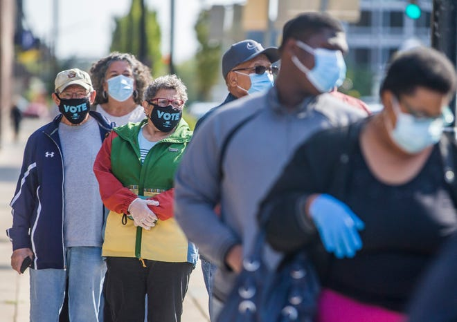 """10/7/2020: Tribune Photo/ROBERT FRANKLIN Paul Swaneck, left, and his wife, Jan Geha, wear face masks that read """"Vote"""" as they stand in a long line on the first day of early voting on Oct. 6, 2020 at the County-City Building in South Bend."""