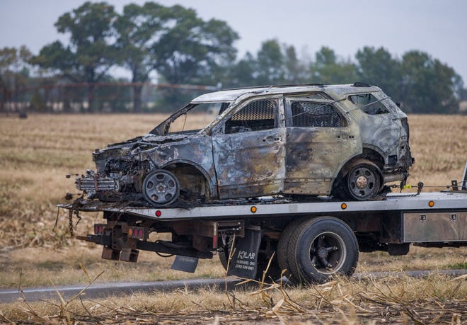 A burned vehicle is towed away from the scene following a police chase and shooting in a cornfield off Leeper Road, near State Road 23, on Monday, Oct. 21, 2019, in Liberty Township.