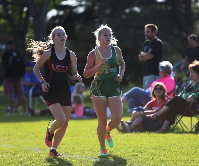 Aberdeen Roncalli's Paige Schmidt, right, keeps with Deuel's Jaycee Hourigan during the beginning of the girls varsity race at Thursday's Roncalli Invite at Lee Park. American News photo by Jenna Ortiz, taken 09/16/2021.