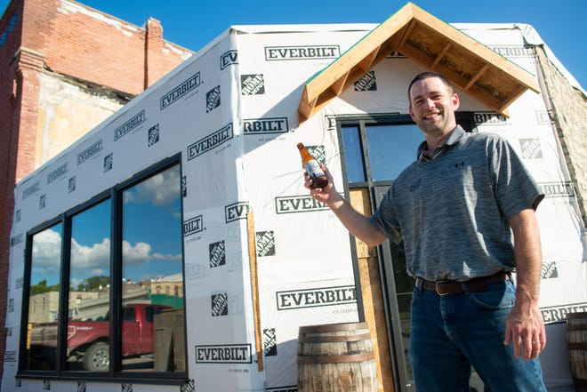 Sean Willcott, owner of Willcott Brewing Co., stands outside of what will soon be a completed tap house connected to his Holton brewery at 219 W. 4th St.