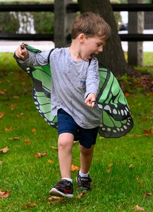 Tommy Martin, 3, runs around wearing butterfly wings as part of the Science Fridays program at the Hamilton-Wenham Public Library on Friday, Sept. 17, 2021.