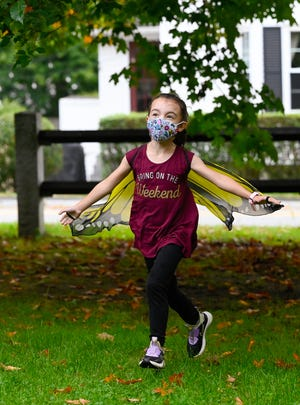 Nora Menchini, 7, runs around wearing butterfly wings as part of the Science Fridays program at the Hamilton-Wenham Public Library on Friday, Sept. 17, 2021.