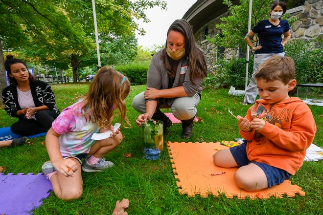 Katie Castelluccio, center, shows a monarch caterpillar to Avery Martin as part of the Science Fridays program at the Hamilton-Wenham Public Library on Friday, Sept. 17, 2021.