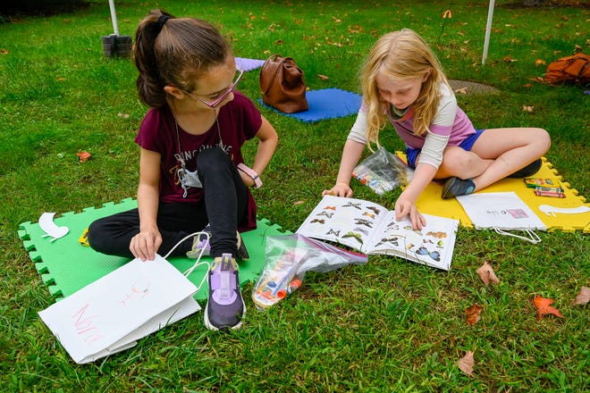 Nora Menchini, 7, and Josie Hribar, 7, look at a book of butterfly stickers during the Science Fridays program at the Hamilton-Wenham Public Library on Friday, Sept. 17, 2021.