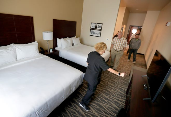 Employee Stacy Steger gives a room tour during the new Cobblestone Hotel grand opening at 208 W. Main St. in Little Chute