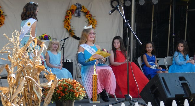 Michaela Duda, 8, center, smiles after being crowned Little Miss Harvest Festival on Thursday evening. This year's princess is Brynn Bruner and the queen isMiya Kinn.