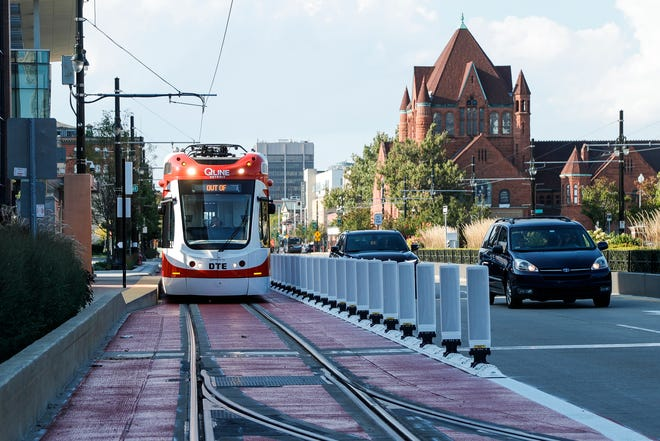 A QLINE streetcar travels on the painted transit-only lane on Woodward Avenue near the Little Caesars Arena in Detroit on Friday.