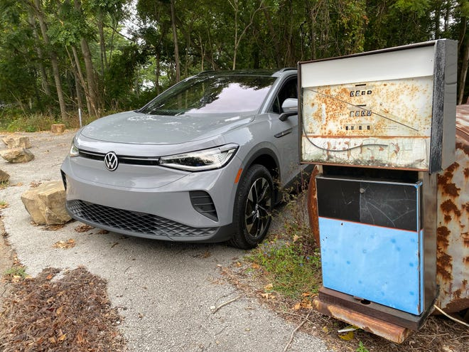 An electric 2021 Volkswagen ID4 AWD SUV sneers at an obsolete gas pump in rural Tennessee.