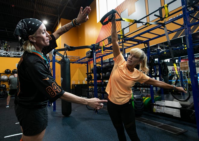 Cape Coral resident Sherry Foley, right, gets instructions from personal trainer Lauren Schaech while using the suspension bodyweight training rig at the recently opened Crunch Fitness location at 58 Nicholas Parkway W. in Cape Coral.