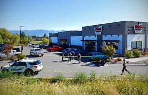 Law enforcement stand at the scene of a fatal shooting outside Fuel Fitness in Kalispell, Mont., on Sept. 16, 2021. A transient man has been arrested and charged in connection with the shooting, authorities said.