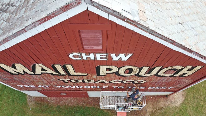 Rusty Baker paints the lettering of the Mail Pouch barn on the corner of Windsor Road and Lakewood Drive.