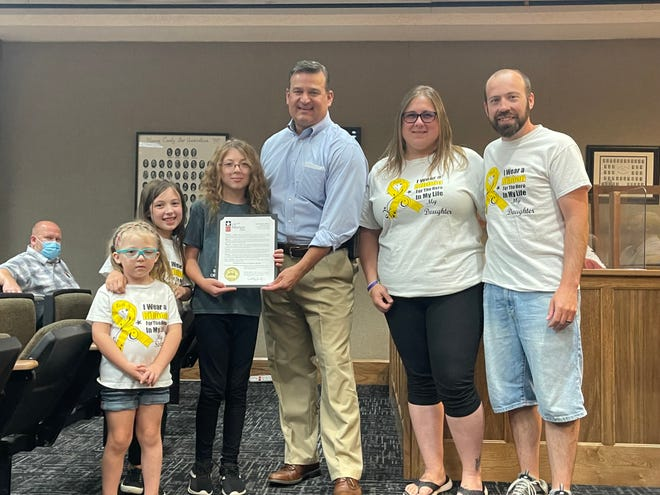 Lexi Edens, 11, holds the city of Marion's proclamation declaring September Childhood Cancer Awareness month alongside her two sisters, Adalynn and Aubrey Edens (white shirts), her parents Kristin and Robert Edens (white shirts), and Marion Mayor Scott Schertzer (blue shirt).